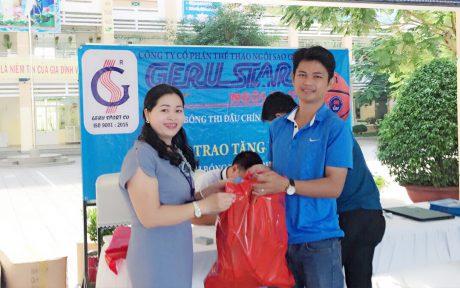 Đại diện Công ty Cp Thể thao Ngôi sao Geru trao bóng tài trợ cho một điểm trường.