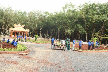 Đoàn viên Thanh niên và công nhân Công ty CPCS Đồng Phú trồng hoa trong khuôn viên di tích đang được tôn tạo. ẢNH: Vũ Phong.