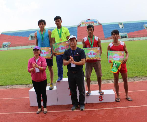 Ông Phan Viết Phùng và bà Nguyễn Thị Hoàng Uyên trao huy chương cho VĐV cự ly 100m nam