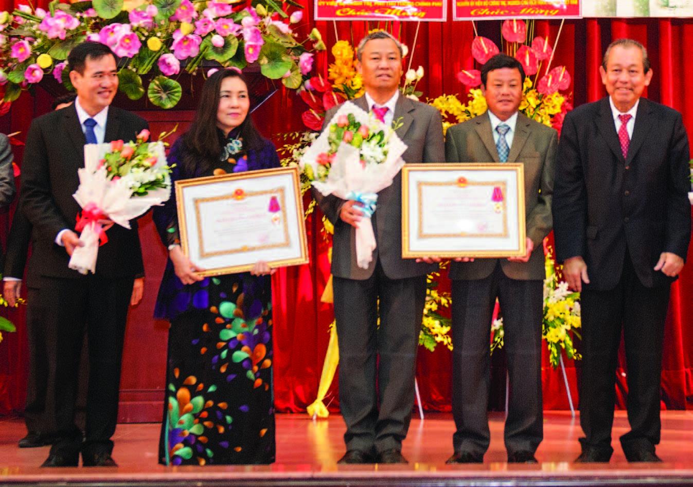 Phó Thủ tướng Chính phủ Trương Hòa Bình (bìa phải) trao Huân chương Lao động hạng Nhất cho lãnh đạo Tạp chí Cao su VN (thứ 1 và 2 bên trái) tại Hội nghị Tổng kết SXKD VRG năm 2016. Ảnh: Tùng Châu
