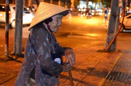 Bà Lục chống gậy đi bán vé số