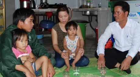 CN Đinh Quý Dương ôm bé Đinh Hà Phương Vy trò chuyện cùng ông Lê Minh Tường trong một chuyến thăm hỏi, tặng quà cho gia đình