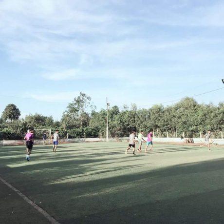 Thanh niên trong làng chơi bóng trên sân cỏ nhân tạo.