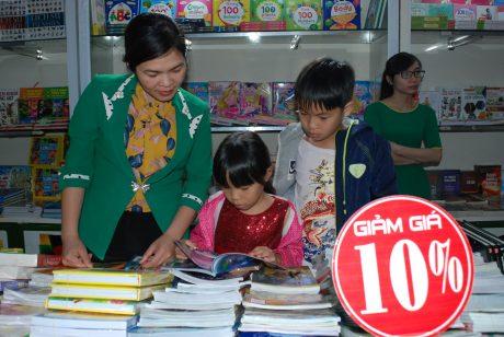 Các em học sinh thích thú đọc sách tại hội sách.