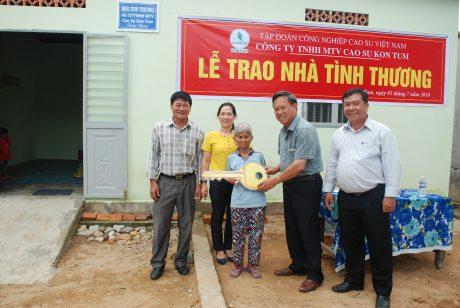 Lãnh đạo công ty Kon Tum và xã Tân Lập trao chia khóa tượng trưng cho hộ Y Reh