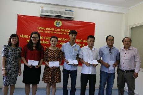 Bà Bạch Thị Phương Chi - Chủ tịch Công đoàn Cao su Krông Buk (ngoài cùng bên trái) và ông Trần Quang Vinh - Chủ tịch Công đoàn Gỗ Thuận An (ngoài cùng bên phải) tặng quà CNLĐ của Tạp chí.