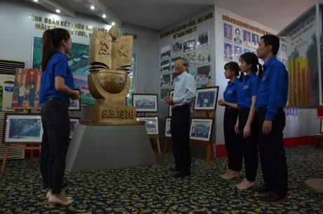Ông Nguyễn Văn Tý đang kể lại lịch sử thành lập công ty cho đoàn viên thanh niên tại phòng truyền thống. Ảnh: Đào Phong
