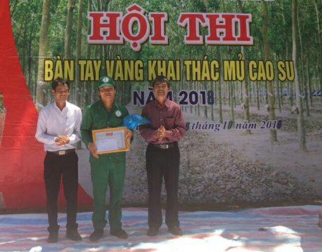 Ông Đặng Ưng_PTGĐ Công ty (bên phải) và Ông Lê Thế Hà_PGĐ Nông trường (bên trái), trao phần thưởng cho Bàn tay vàng Hà Văn Duyên