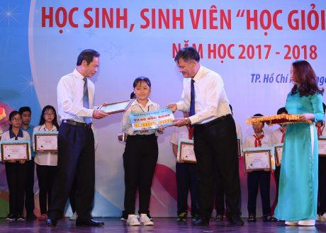 Ông Trần Ngọc Thuận – Bí thư Đảng ủy, Chủ tịch HĐQT VRG và ông Võ Sỹ Lực – nguyên Chủ tịch HĐTV VRG trao thưởng cho học sinh. Ảnh: Vũ Phong.