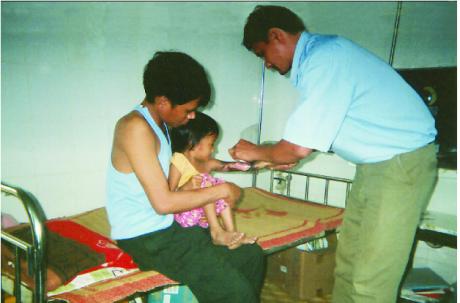 Y sỹ Hà Phẩm Chất đang chăm sóc vết thương cho cháu H'Nha