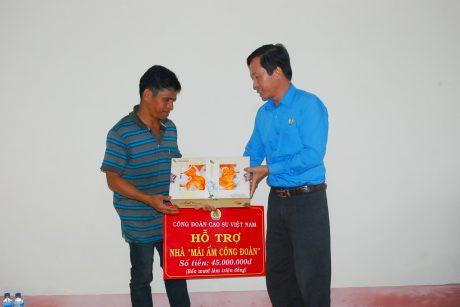 Chủ tịch Công đoàn Công ty TNHH MTV Cao su Chư Prông Trần Văn Tiến tặng quà cho anh Biên nhân dịp có nhà mới