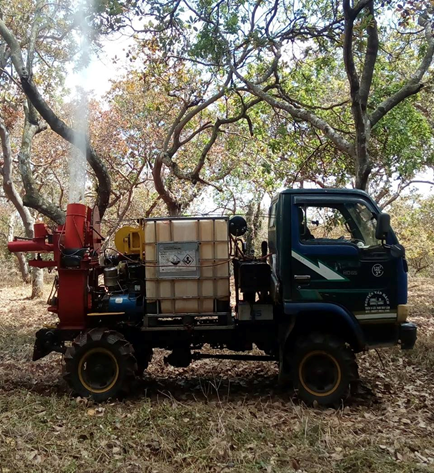 Máy đa năng đang thực hiện phun thuốc trên vườn cây.