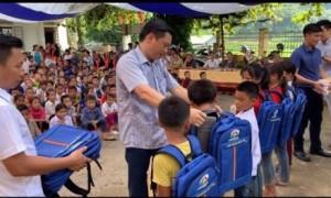 Đại diện lãnh đạo Tập đoàn Quế Lâm trao quà cho các em học sinh.