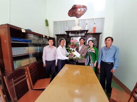 ông Trương Công Lực – Chủ tịch Công đoàn công ty TNHH MTV Cao su Ea H'Leo trao hoa cho ông Phạm Văn Khôi (mặc áo vét nâu) – Giám đốc Trung tâm bồi dưỡng chính trị huyện.